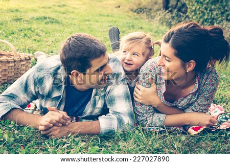Happy family of three lying in the grass in autumn. Warm effect added. - stock photo