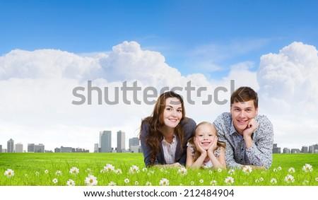 Happy family of three lying on green grass - stock photo