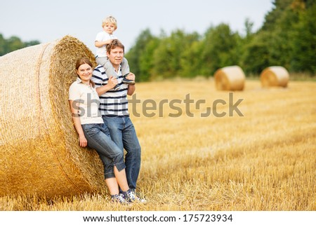 happy family of three: mother, father and little toddler son on yellow hay field in summer - stock photo