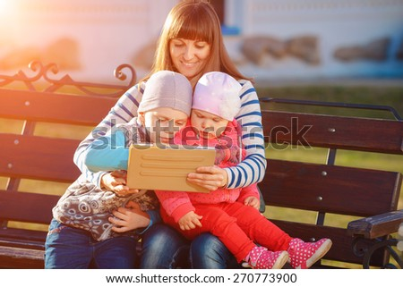 Happy family of three, mother, son and daughter sitting on a bench in the afternoon in the city park and are holding a tablet, a beautiful spring weather, the sun is shining