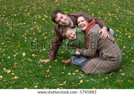 Happy family of three on the grass covered with fallen leaves - stock photo