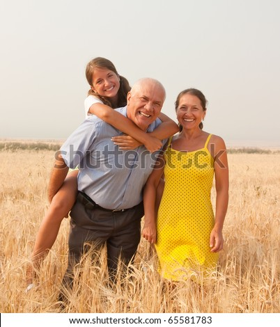 Happy family of three over a field of wheat - stock photo