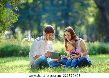 Happy family of three people relaxing in a city park. Father shows in tablet funny pictures. Family sitting on grass and looking at the tablet. Happy family concept of the good life.  - stock photo
