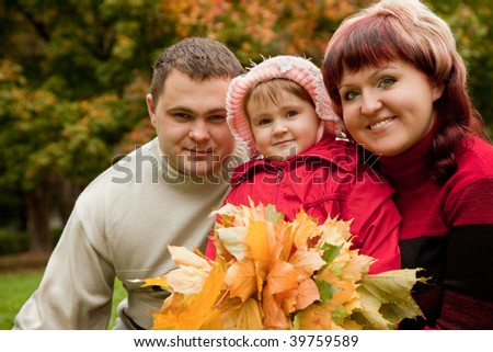 happy family of three persons in the autumn park - stock photo
