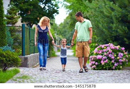 happy family of three persons walking the street - stock photo