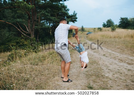 Happy family of three playing and laughing while sitting on grass outdoors, beatuful forest.