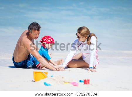 Happy family of three playing on the beach, putting their hands on top of each other. Concept of unity, protection and happiness. - stock photo