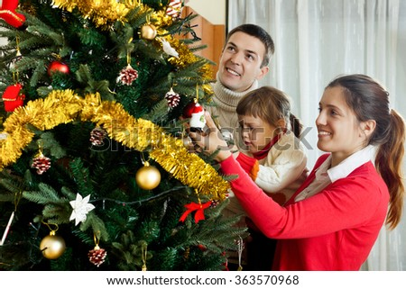 Happy family of three preparing for Christmas at home - stock photo
