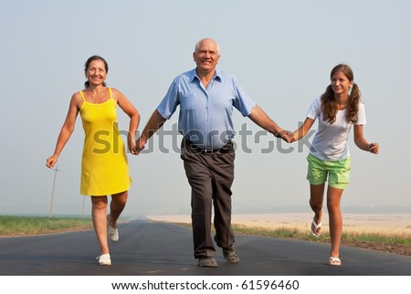 Happy family of three run over a  road at summer