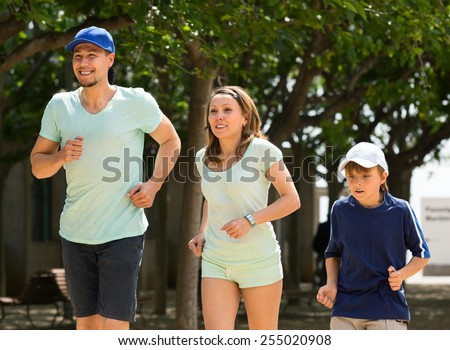 Happy family of three running in summer morning - stock photo