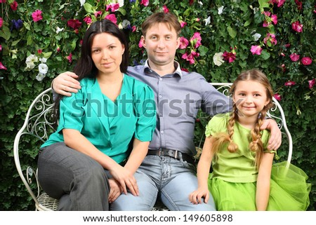 Happy family of three sit on white bench in garden near verdant hedge. - stock photo