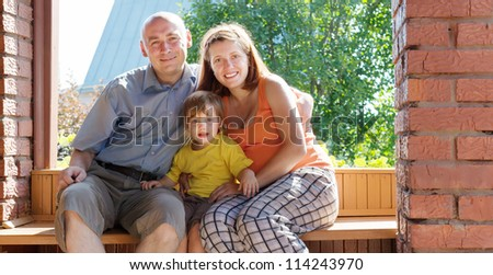Happy family of three sits on bench in summer veranda - stock photo