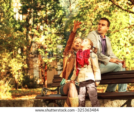 Happy family of three sitting on a bench and enjoying the autumn day. - stock photo