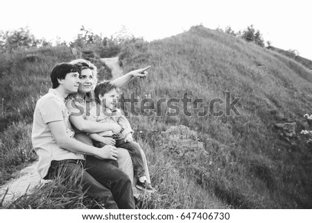 happy family of three sitting on the hill in summer time - black and white. Love, Vacations and Happy Family Concept.