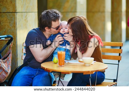 Happy family of three spending their family time together in an outdoor cafe, father is kissing his adorable little son  - stock photo