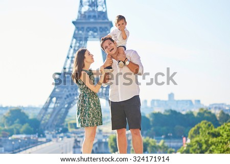 Happy family of three standing in front of the Eiffel tower and enjoying their vacation in Paris, France