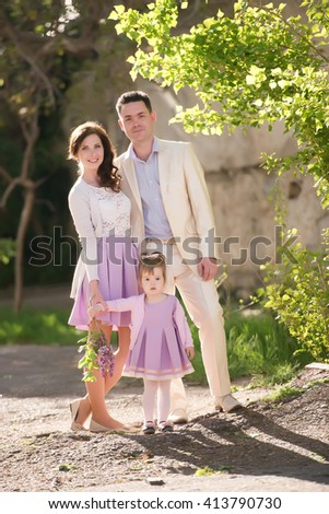 happy family of three standing under a tree in the bright sunlight