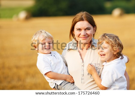 Happy family of three: two little twins boys and young mother  having fun on yellow hay field in summer - stock photo