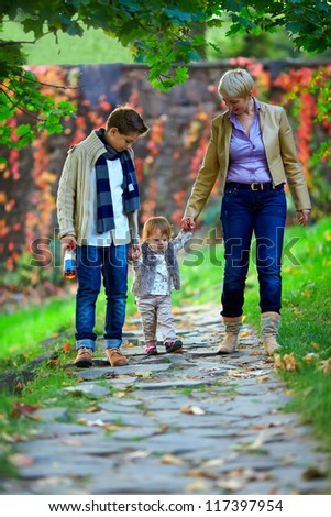 happy family of three walking the autumn park - stock photo