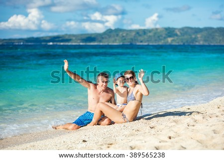 Happy family of three waving hands while having fun on the beach - stock photo