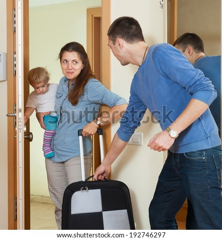 Happy family of three with child with luggage leaving the home