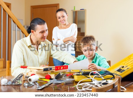 Happy family of three with teenage boy doing something with the working tools - stock photo