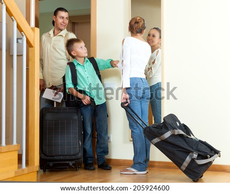 Happy family of three with teenage son with luggage leaving the home