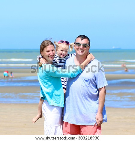 Happy family of three - young active parents with cute toddler daughter - enjoying summer vacation together on the beach at the sea - stock photo