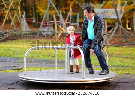 Happy family of two, active father with his adorable daughter, cute blonde toddler girl, wearing warm red duffle coat, playing together at playground in the park on sunny day - stock photo