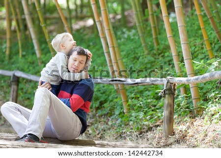 happy family of two enjoying time together outdoors; cute little boy hugging his father - stock photo