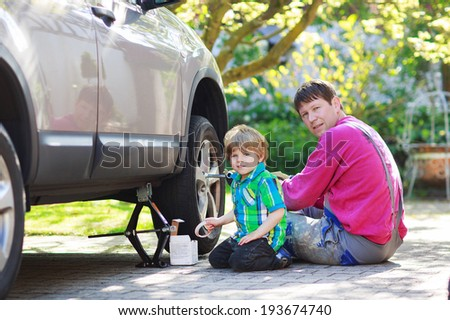 Happy family of two: father and adorable little boy repairing car and changing wheel together on warm day, outdoors. - stock photo