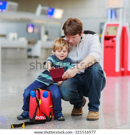 Happy family of two: Father and little son at the airport, traveling together and holding passport in hand.
