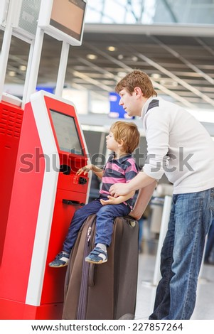 Happy family of two: Father and little son at the international airport, traveling together and checking in at terminal. Going on a journey. - stock photo