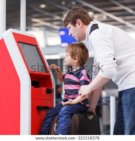 Happy family of two: Father and little son at the international airport, traveling together and checking in at terminal. - stock photo