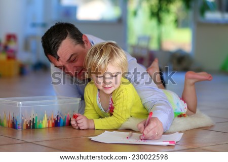 Happy family of two, loving caring father with child, adorable toddler girl, spending time together at home lying cozy on tiles floor on warm lambskin drawing picture with colorful felt-tip pencils - stock photo