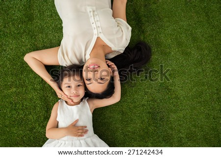 Happy family of two lying on the grass, view from above - stock photo