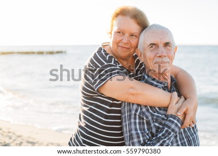 Happy family of two mature people hugging outdoors. Senior smiling couple standing on beach near sea on sunset.