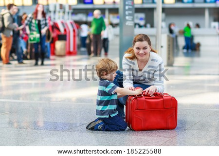 Happy family of two: Mother and little son at the airport, traveling together.