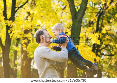 Happy family of two people laughing and playing in autumn wood. Daddy and son at orange trees background on sunny warm fall day.  - stock photo