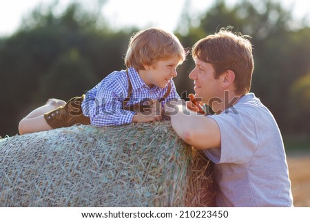 Happy family of two: Young father and his little son having fun on yellow hay field in summer - stock photo