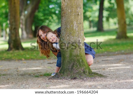 Happy family of two:  young mother and adorable baby daughter playing together hiding in summer park and having fun together, outdoors. - stock photo