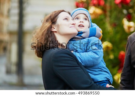 Happy family of two, young mother and her little son near decorated Christmas tree