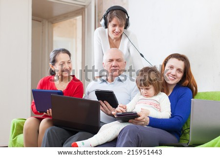 Happy family of with various portable computers on sofa