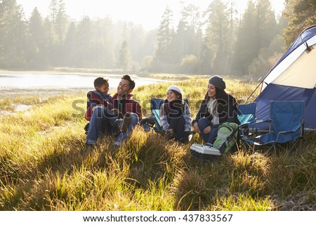 Happy family on a camping trip relaxing by their tent