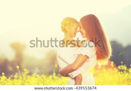 Happy family on a summer meadow. little girl child baby daughter hugging and kissing mother - stock photo