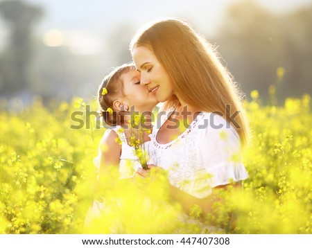 Happy family on a summer meadow. little girl child daughter hugging and kissing mother - stock photo
