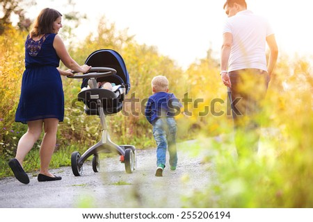 Happy family on a walk in nature enjoying life together. - stock photo