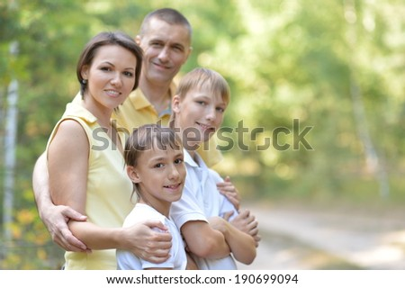 Happy family on a walk in the park - stock photo
