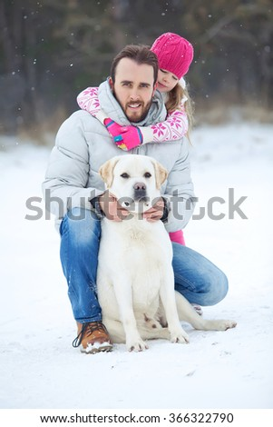 Happy family on a winter day, smiling father and baby walking with his dog in the park