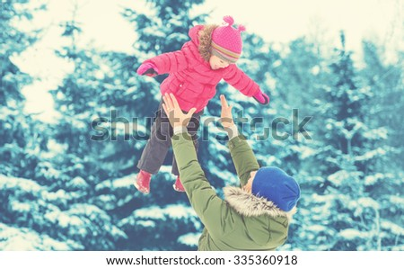 Happy family on a winter walk in nature. Dad throws up baby girl - stock photo